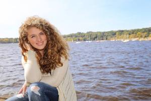 Mackenzie sits beside the St. Croix River on a sunny day.